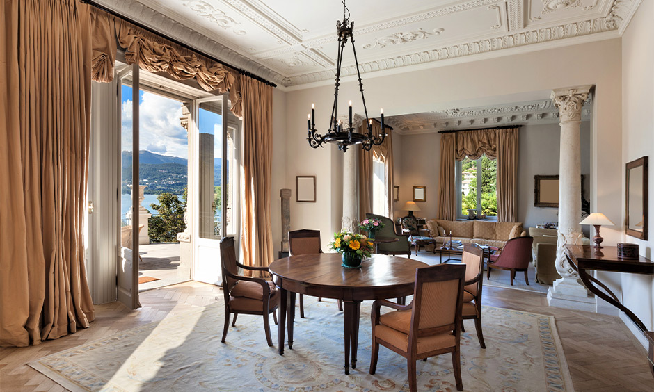 French interior dining area design with candlestick chandelier, rustic-looking drapes, and round dining table brings charm.