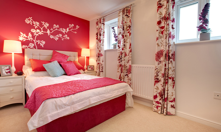 Bedroom pink color combination for wall with floral printed curtains and pink cushions adds vibrance to space.