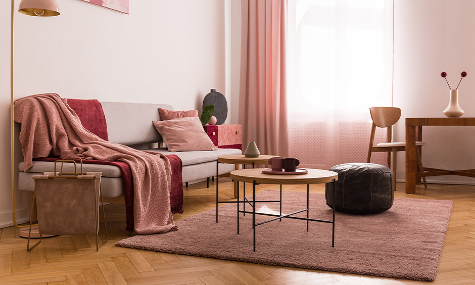 The living room has multiple shades of pink color combination for the wall with pink lampshades, pillows, and drapes.