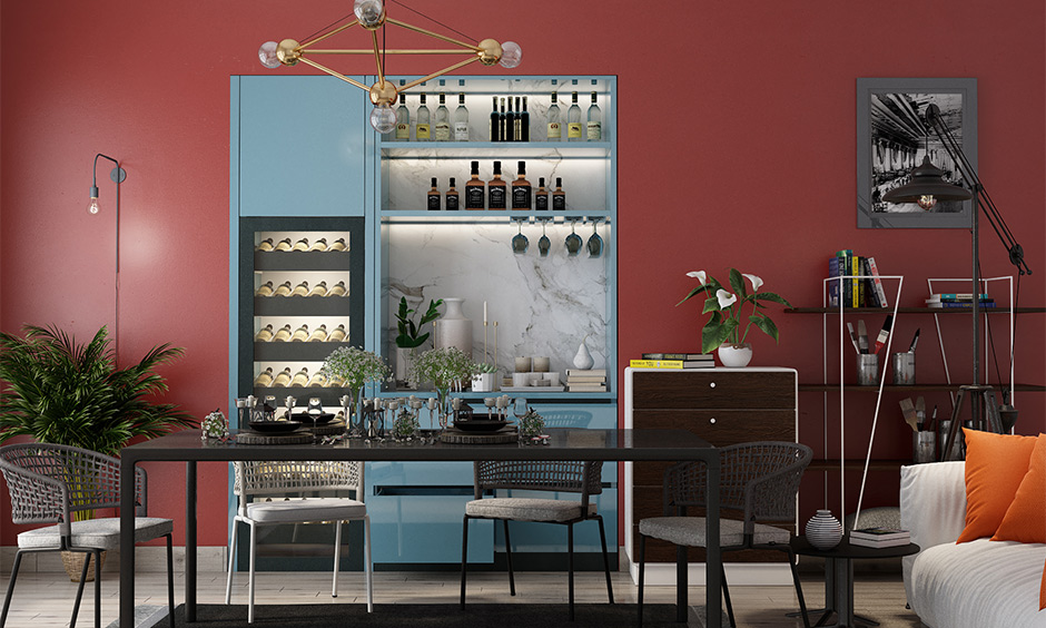 Dining room in dark pink color combination for wall with blue and grey furniture adds bold to space.