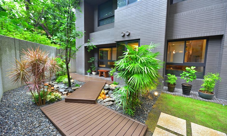 A small backyard with a wooden path and small pebbles surrounded by plants is a gardening idea for home in India.