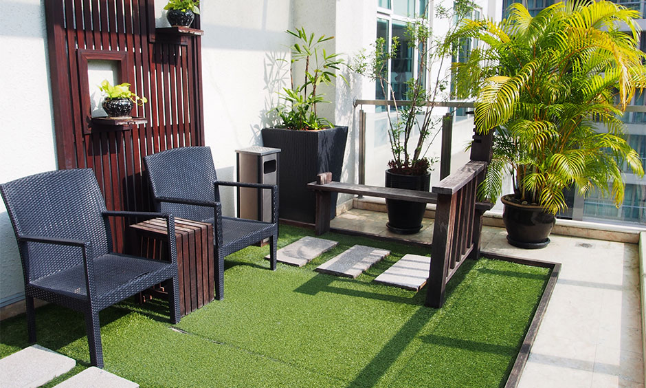 A small terrace with rattan chairs surrounded by potted plants and a patch of grass is a simple home garden idea.