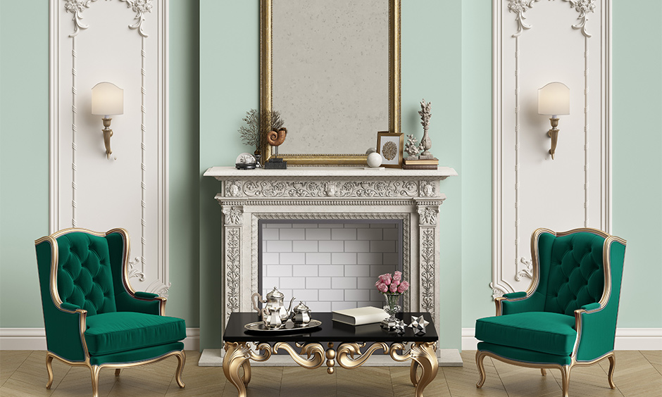 Old-style living room home colour matching with white wall moulding frames and green armchairs look classy.