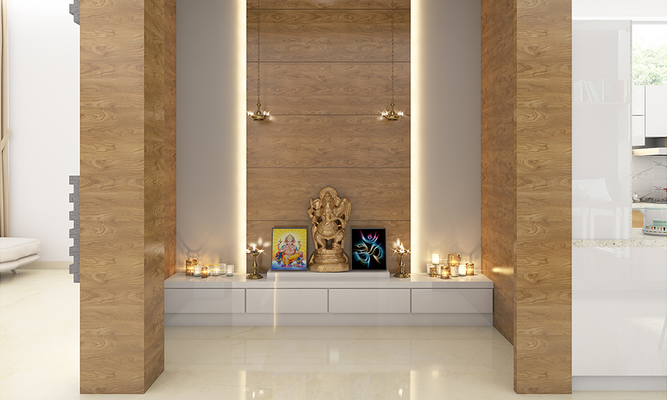 Pooja room cupboard designed in a modern look with white lamination brings an elegant look.