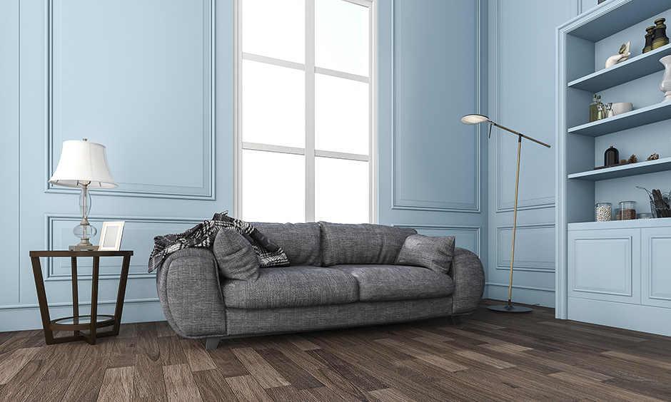 The dark brown wood laminate flooring design in the pastel blue living room looks charmed and chic.