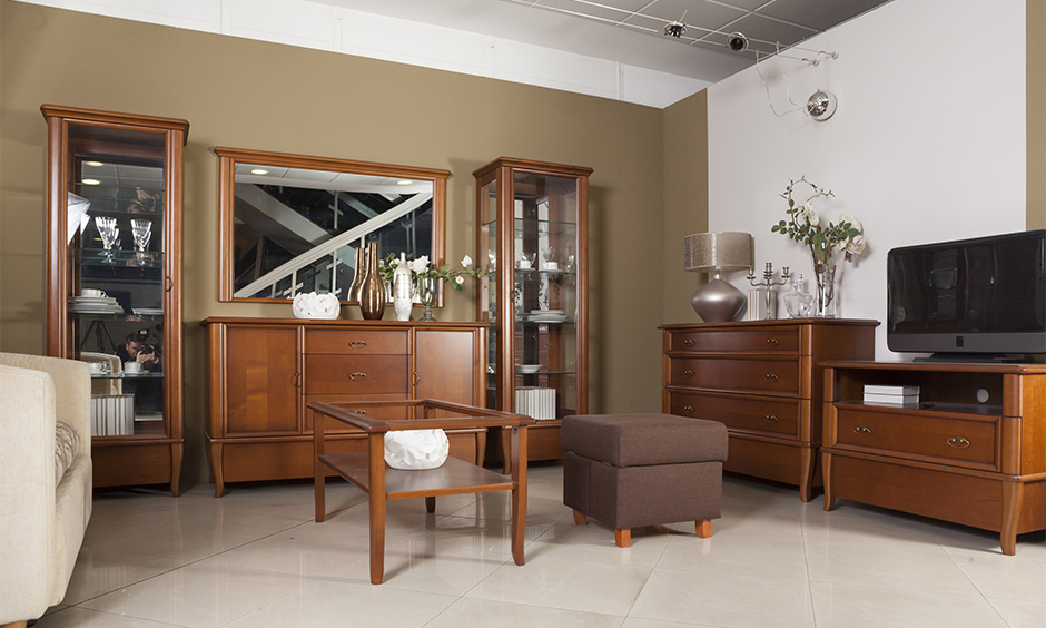 Vintage wooden showcase design for hall with glass door adds classic look with elegant furniture in the living room.