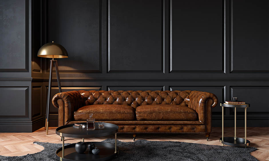 Two-seater Chesterfield leather sofa against the black wall lends a classic vintage look is the trending sofa design.
