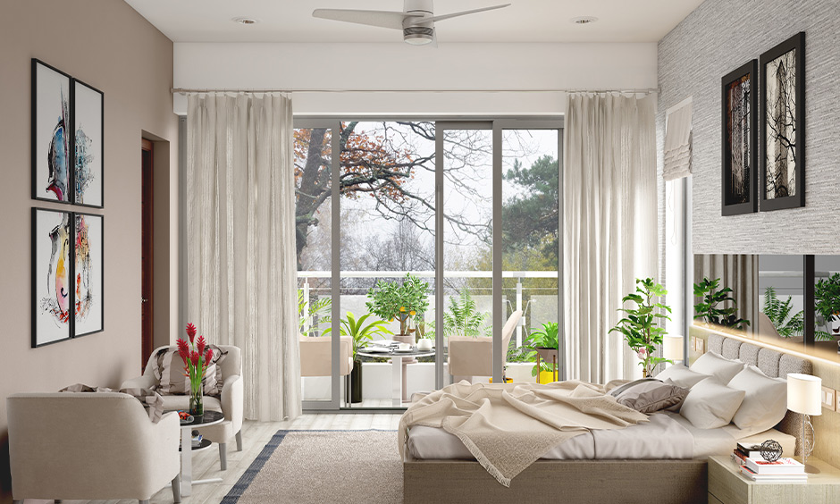 An aluminium glass sliding door designed between bedroom and balcony with white curtains lend a sleek look.