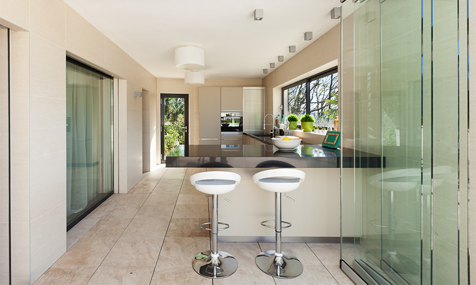 The partition between the living and kitchen with sliding glass door design lends a chic look to the area.