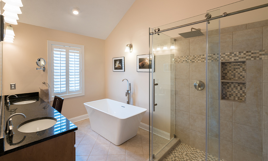 Shower area separated from rest of the bathroom with sliding glass door design for bathroom look spacious.