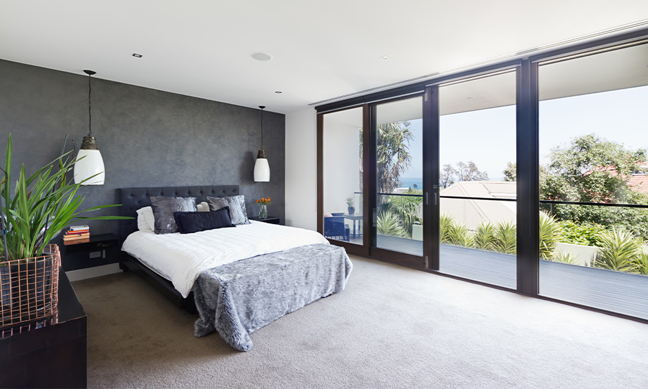 The bedroom's glass sliding door design with a wooden frame lends an elegant look and chic wooden glass sliding door design.