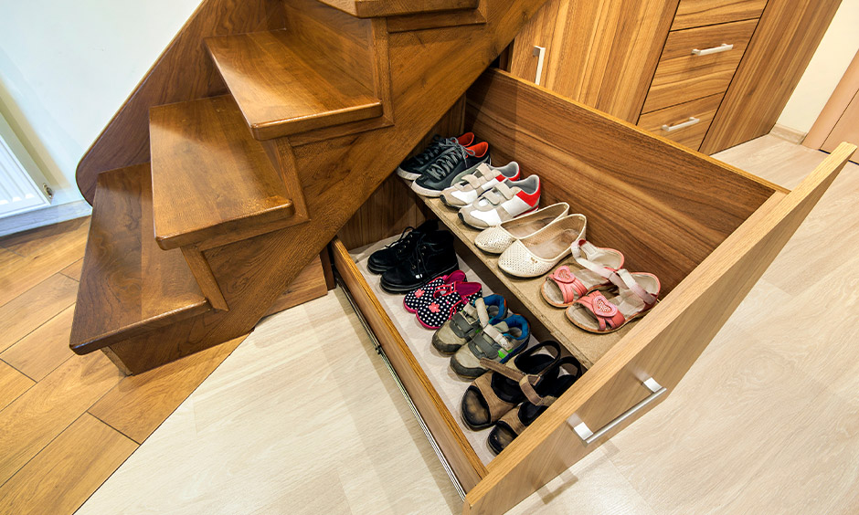 Space-saving shoe rack, pull out shoe drawers under the staircase with inbuilt organisers to keep shoes intact.