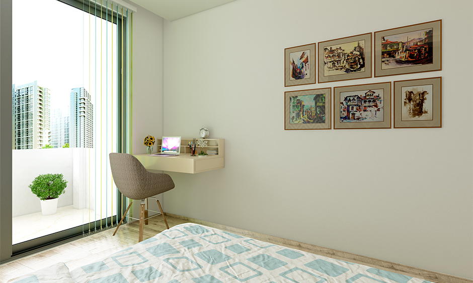 A wall-mounted space-saving home office desk against a white wall with minimal design in the bedroom looks aesthetic.