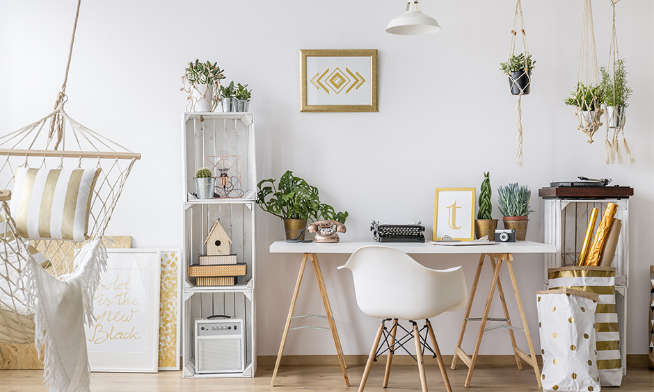 All-white study room decoration with indoor plants, photo frames, wooden rack and jute hammock swing add an old-school vibe.