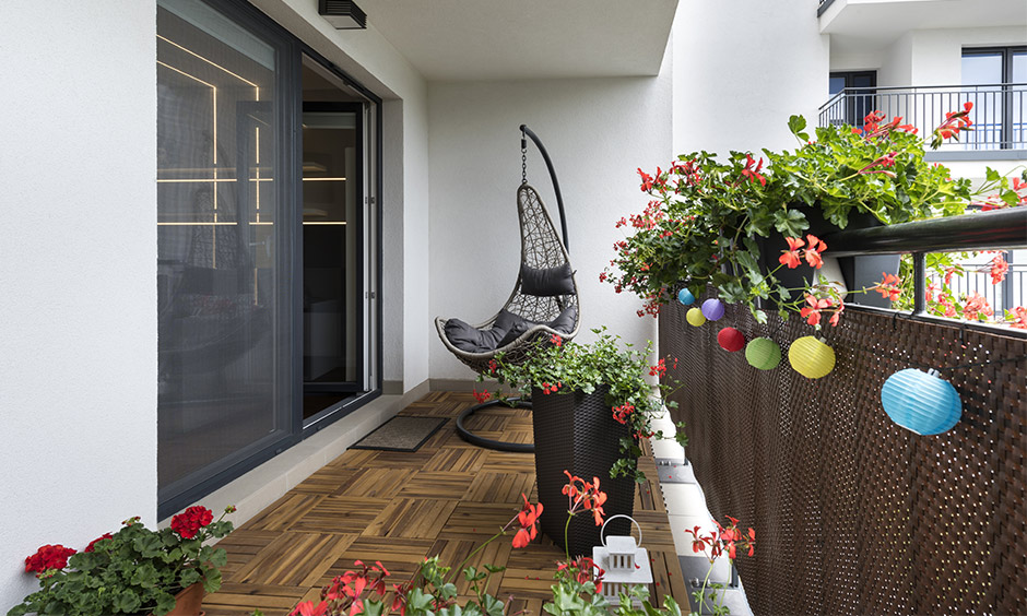 Balcony with a movable swing, potted plants and wooden flooring is the best interior hack for a busy mom.