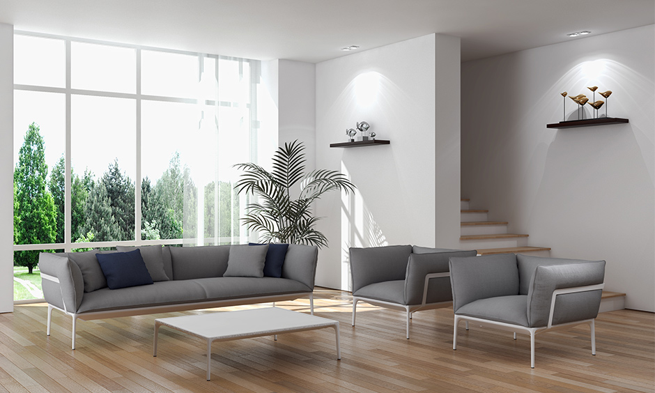 A white living room with stairs hidden behind a wall with wooden steps created a minimalistic look.
