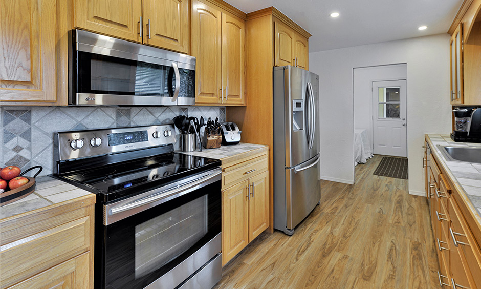 Parallel kitchen cabinets Indian style made from wood with backsplash tiles lends a rustic look.