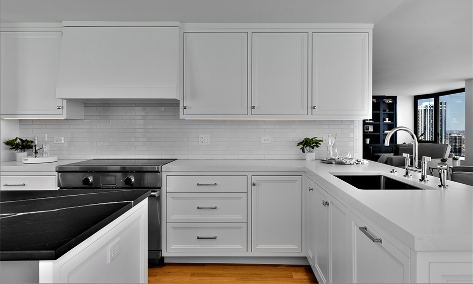 The black kitchen island countertop with white shaker style kitchen cabinets in glossy finish look pure and attractive.