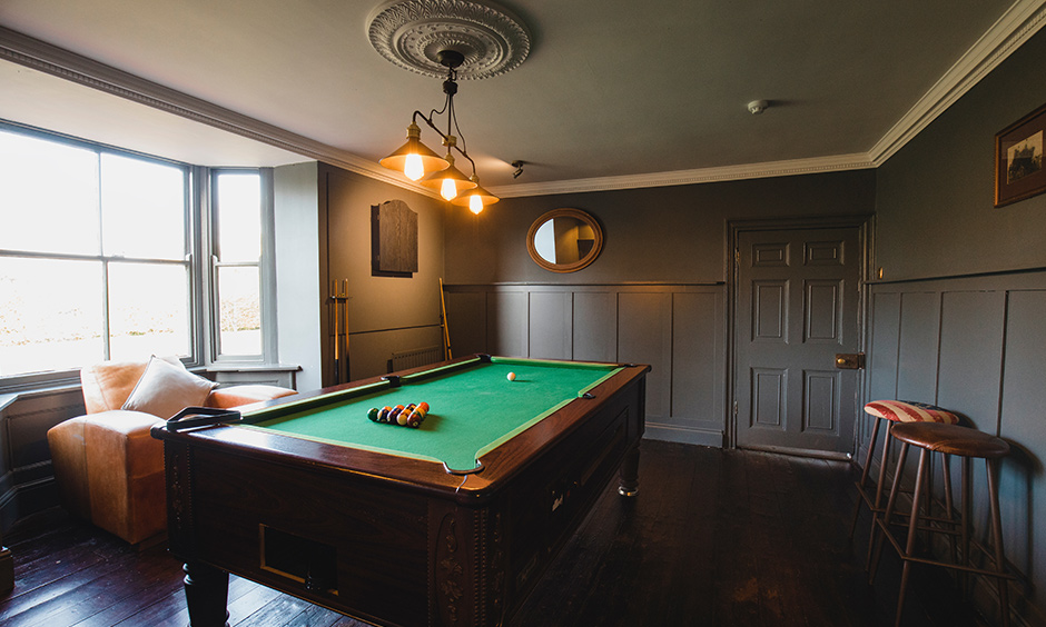 Pool table gaming room designed in grey colour with classic lights and table looks vintage.