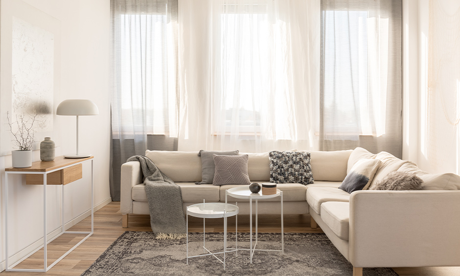 A white Scandinavian living room with a huge window and long floor curtains let in natural sunlight and a fresh vibe.