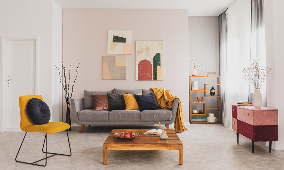 Scandinavian living room with colourful cushion, chair and grey sofa complements the minimalist style.