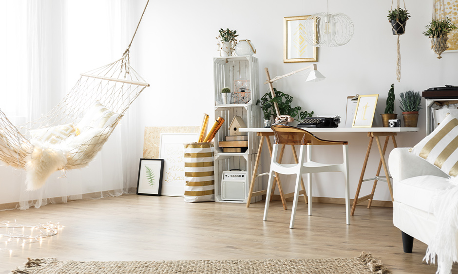 Scandinavian living room with a hammock, wooden flooring and hanging plants creates a beach vibe.