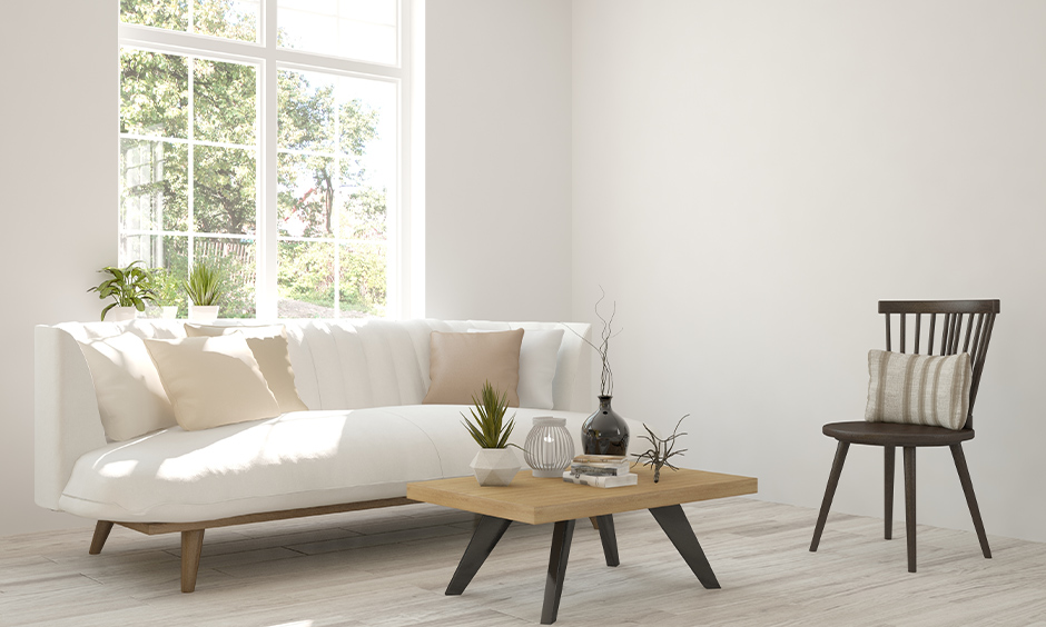 White Scandinavian living room with simple wooden furniture and minimal accessories lends a welcoming vibe.