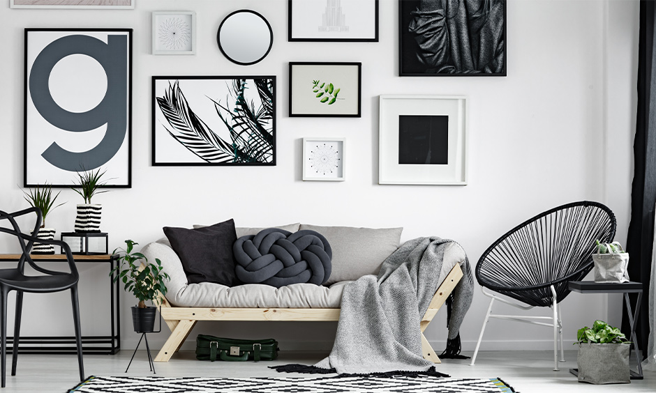 White Scandinavian living room with painting frames on the wall lends an aesthetic look to the area with unique furniture.