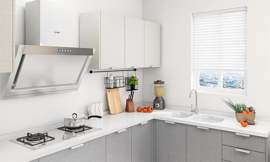 All-white Indian kitchen interior design has a window rolling shutter in minimalistic design.