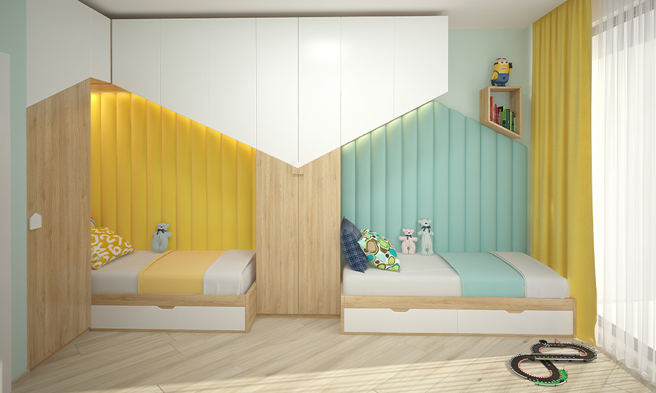 Back to back twin space saving kids beds made from light wood and side headboard in yellow and blue.