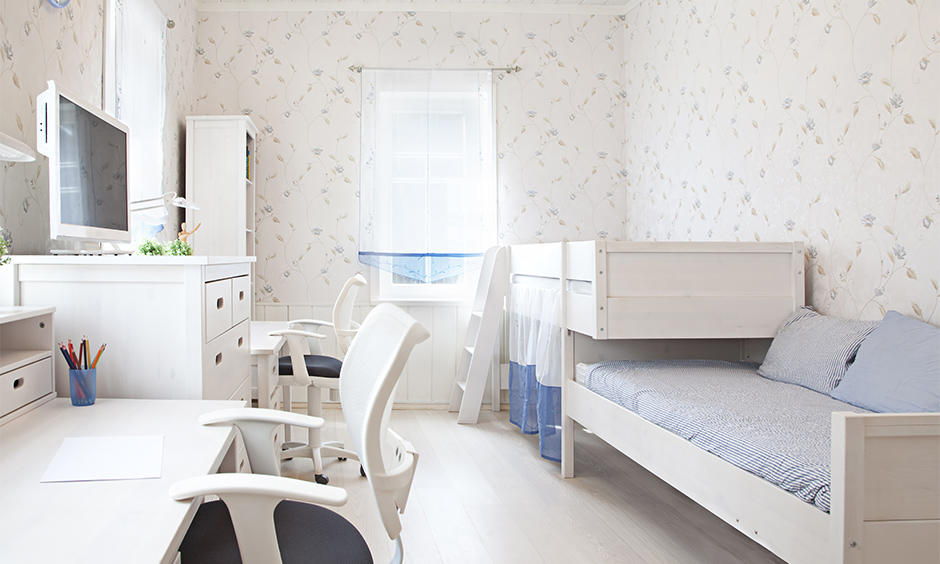 The small bedroom has a space-saving kids bed with an attached sofa bed in white colour that seems spacious and welcoming.