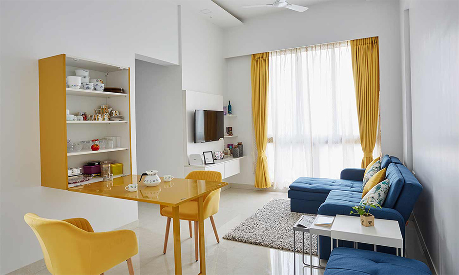 A small living room cum dining area with a yellow foldable dining table is creative space-saving living room furniture.