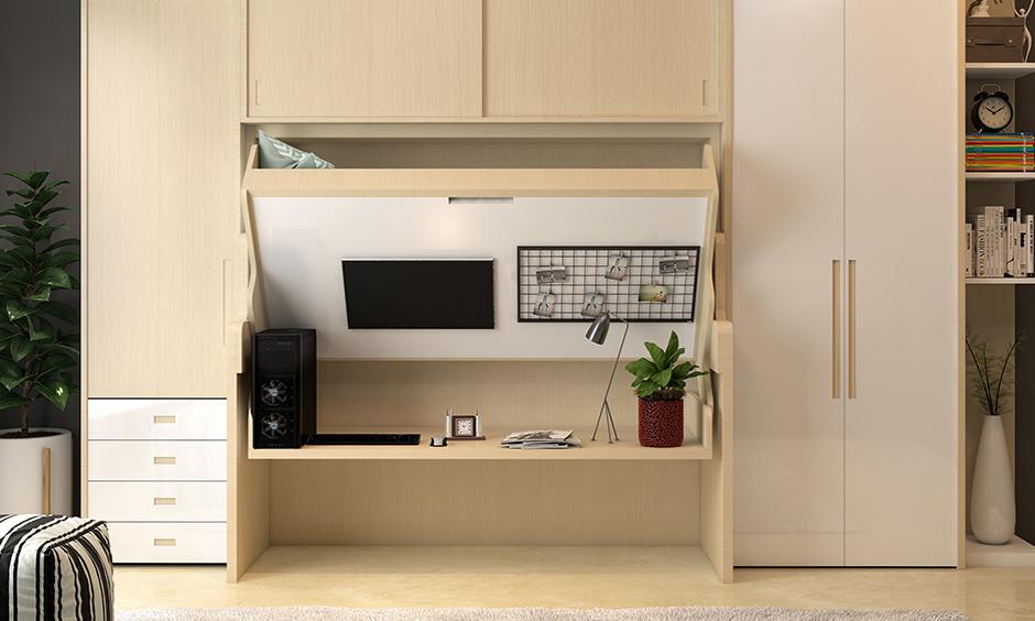Multi-purpose furniture idea, wardrobe cum study desk cum bed in the wooden finish is the space-saving design.