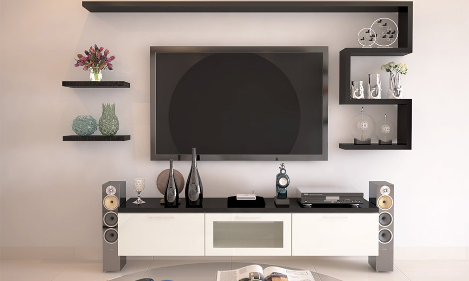 The wall-mounted tv cabinet design idea in black and white with floating shelves gives it an edgy look.