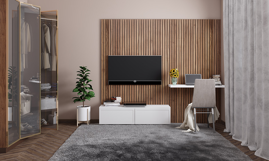 A wall-mounted tv cabinet with wooden panelling as a backdrop adds to aesthetics.