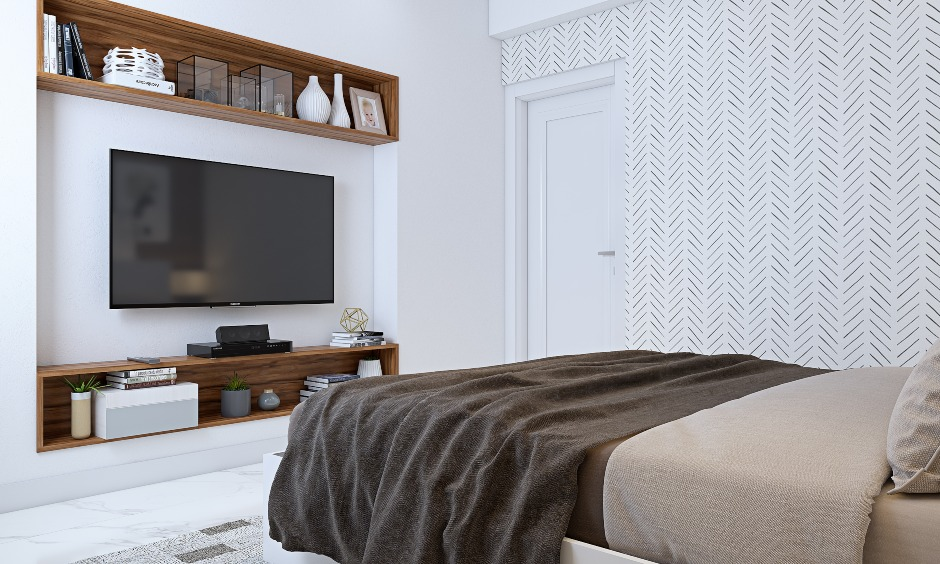 white bedroom with tv unit and floating wooden shelf in 3bhk home interior design in india