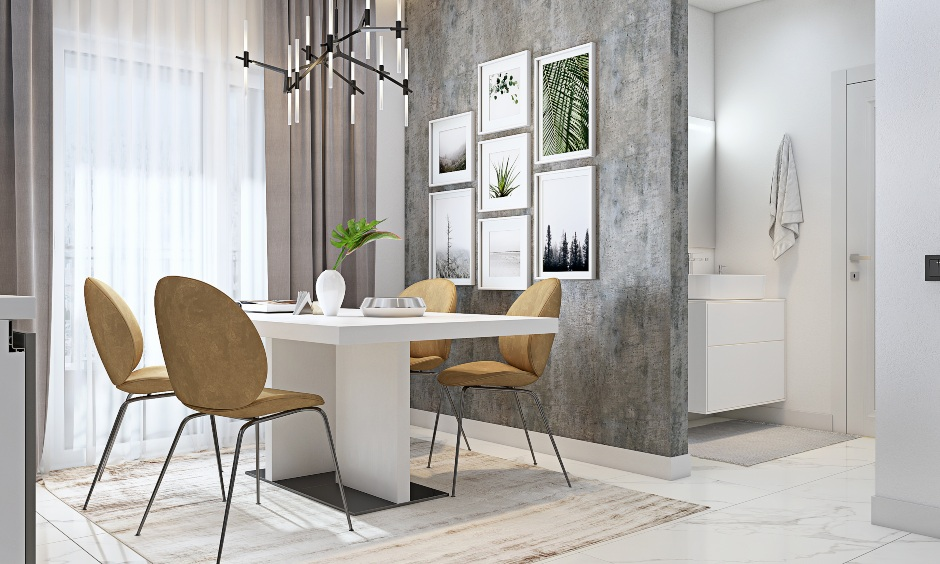 Dining area has a white dining table and four armless chairs in 3bhk flat interior design