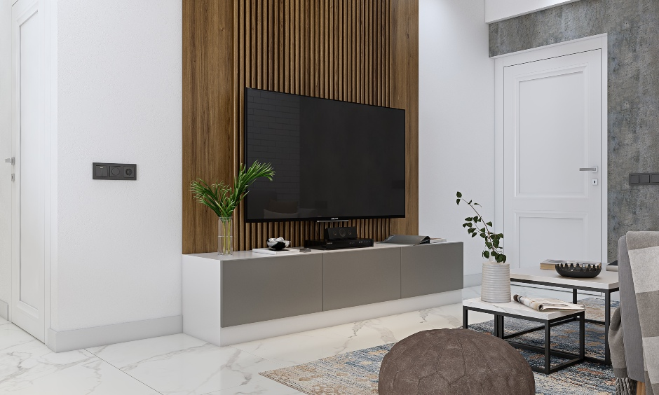 3 bhk house has tv unit with wooden panel background