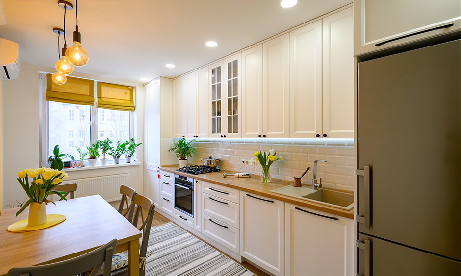 Modern straight kitchen design with white wooden cabinets and large pantry cabinet
