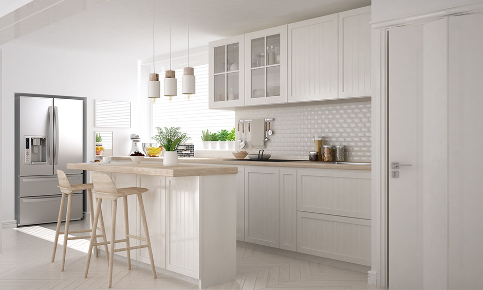 Straight line modular kitchen design with island with high stools and stylish looking pendant lights